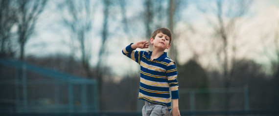 Caucasian autistic boy in striped shirt pretends to throw a ball outside