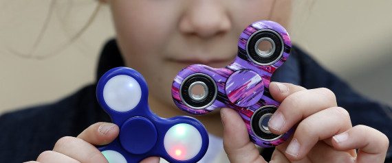 """PARIS, FRANCE - MAY 20:  In this photo illustration, a child shows a """"Hand Spinner"""" on May 20, 2017 in Paris, France. The """"Hand Spinner"""" is a toy that sits like a propeller on a person's finger, with blades that spin around a bearing. Since a month the """"Hand spinner"""" or """"Fidget spinner"""", a whirligig from the United States has become a mondial phenomenon to the point of creating stock shortages in toy stores.  (Photo Illustration by Chesnot/Getty Images)"""