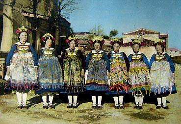 Τέλη δεκαετίας του 1960: Λαζαρίνες της Αιανής με πλήρη εορταστική εξάρτηση ποζάρουν στο προαύλιο της οικίας της οικογένειας Καλλιανιώτη. Δεξιά διακρίνονται οι οικίες Ασημίνα και Νικολάου. Στη μέση πίσω το ύψωμα Κούλια (Αρχείο Δημοτικού Σχολείου Αιανής)
