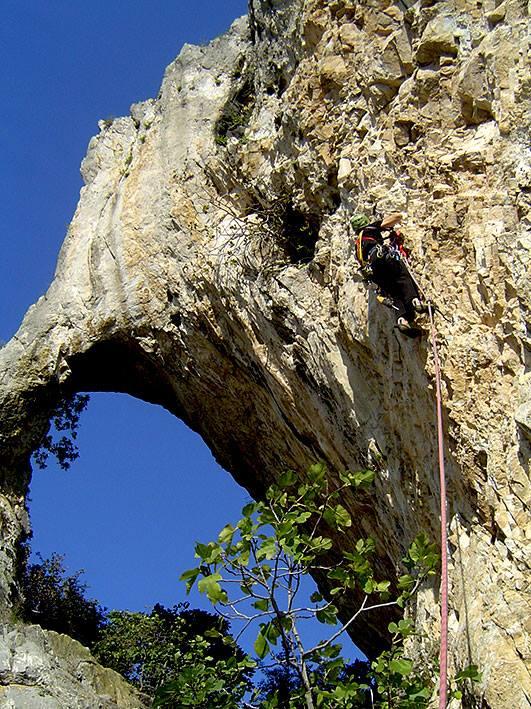 Τοποθετώντας ιμάντα σε μυτίκι, ώστε να λάβει χώραν προώθηση, αρχικά ως τη σπηλιά που διακρίνεται μερικά μέτρα επάνω αριστερά. Ο συμπαγής βράχος δεχόταν ελάχιστες παροδικές ασφάλειες (ψείρες ή καρφιά), αυξάνοντας την επικινδυνότητα και την απορρέουσα πρόκληση. Πιο συγκινητικό όλων ήταν η αιώνια ιερότητα του «Τρύπιου Βράχου», καθώς οι γυναίκες πίστευαν –και πιστεύουν ακόμα- ότι βοηθάει στην τεκνοποίηση. Εμάς, πάντως, μας πρόσφερε σθένος για τον άφοβο δαμασμό του. Φωτό Teo Fasoulas — στην τοποθεσία Néa Zoí, Pella, Greece.