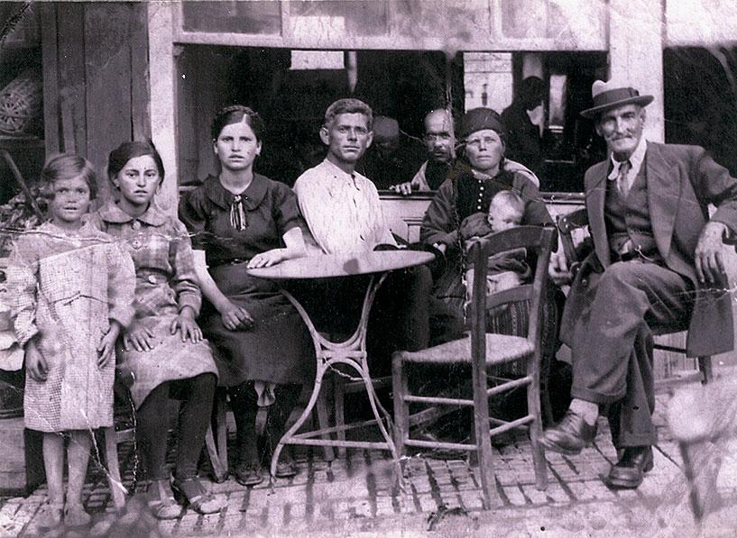 Ο Ιωάννης Γιαννάκης ή Στάμος με το άσπρο πουκάμισο , υπεύθυνος του ΕΑΜ Αιανής. Εικονίζεται στα κελιά του μοναστηριού της Παναγίας, που μετατράπηκαν σε καφενεία και παντοπωλεία μετά το 1912. Κατεφαδίστηκαν  αρχάς δεκαετίας του 1950. Ιδιωτική Συλλογή Σωκράτη Γιαννάκη.