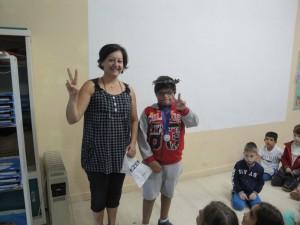 Η κα Χρύσα και ο Μαρίνος από την Ε΄τάξη ως άλλος αθλητής με κότινο και μετάλλιο σχηματίζουν το σήμα της νίκης