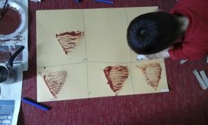 2. Βουτήξαμε τα σχήματα σε καφέ μπογιά και τα πατήσασμε σε κίτρινο κάνσον δημιουργώντας το αποτύπωμά τους.