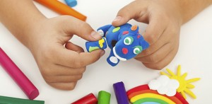 Child playing with colorful clay making animal figures – closeup on hands