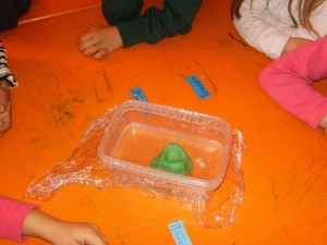 Βάλαμε νερό σε ένα μπολ,φτιάξαμε ένε βουνό από πλαστελίνη  με  μια μικρή κοιλότητα στηυν κορυφή, σκεπάσαμε  με σελοφάν...