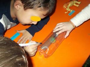 Αφού κόψαμε ένα μπουκάλι πλαστικό σημειώσαμε, με τη β οήθεια ενός χάρακα τις γραμμούλες και γράψαμε τους αριθμούς  μέχρι το 5.
