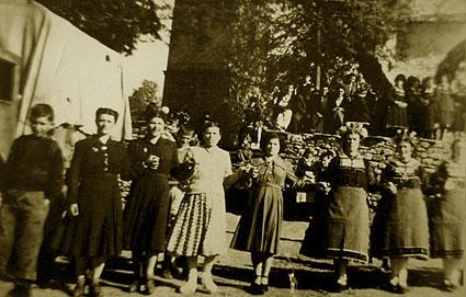 Πλατεία Λευκοπηγής 1950. Παράδοση και νεωτερισμοί. Φορτηγό αυτοκίνητο στο φόντο αριστερά και δυτικού τύπου ένδυση των πρώτων γυναικών σε αντιδιαστολή με την παραδοσιακή των υπολοίπων όσο και της τοιχοδομίας. Οι στολές άρχισαν να αλλάζουν για τις γυναίκες από το 1945 φερμένες από την Ούνρα, ιδιαίτερα δε κατά τη διάρκεια του Εμφυλίου Πολέμου όταν οι γυναίκες κατέφευγαν ως ανταρτόπληκτες στην πόλη της Κοζάνης (Αρχείο ΕΜΑΣ Μέγας Αλέξανδρος Λευκοπηγής)