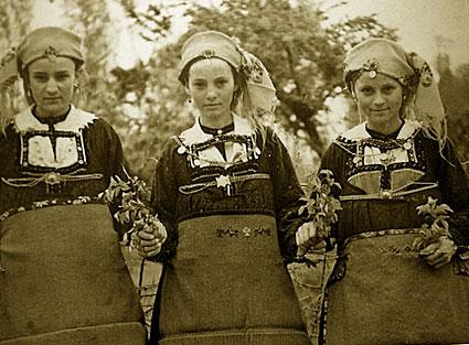 Λαζαρίνες της Λευκοπηγής με την παραδοσιακή τους στολή κρατώντας άνθη. Στην ποδιά της μεσαίας διακρίνονται αντωπά κεντημένα σχέδια, πουλιά και φυτά (Αρχείο ΕΜΑΣ Μέγας Αλέξανδρος Λευκοπηγής)