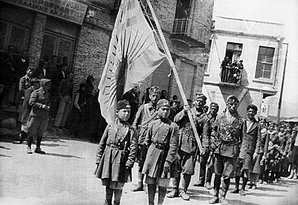 Αντάρτες του ΕΑΜ-ΕΛΑΣ εισέρχονται στην πλατεία Αιμιλιανού [Γρεβενών], 25 Μαρτίου 1943. Στην πρώτη γραμμή της πορείας διακρίνονται τα «αετόπουλα» της Ενιαίας Πανελλαδικής Οργάνωσης Νέων (ΕΠΟΝ) με μακεδονικούς ντουλαμάδες. Ακολουθούν Ελασίτες που φέρουν σημαία με κόκκινο ακτινωτό ήλιο. Στο πίσω μέρος της φωτογραφίας φαίνεται η οικία Σιώζου και στο βάθος το καμπαναριό του ναού Ευαγγελισμού της Θεοτόκου (Ευαγγελίστρια).  πηγή: http://www.thinkfree.gr/thinkculture/%CE%B3%CF%81%CE%B5%CE%B2%CE%B5%CE%BD%CE%AC-%CE%BF%CE%B3%CE%B4%CF%8C%CE%BD%CF%84%CE%B1-%CF%87%CF%81%CF%8C%CE%BD%CE%B9%CE%B1-%CF%86%CF%89%CF%84%CE%BF%CE%B3%CF%81%CE%B1%CF%86%CE%AF%CE%B5%CF%82-1895-1-2